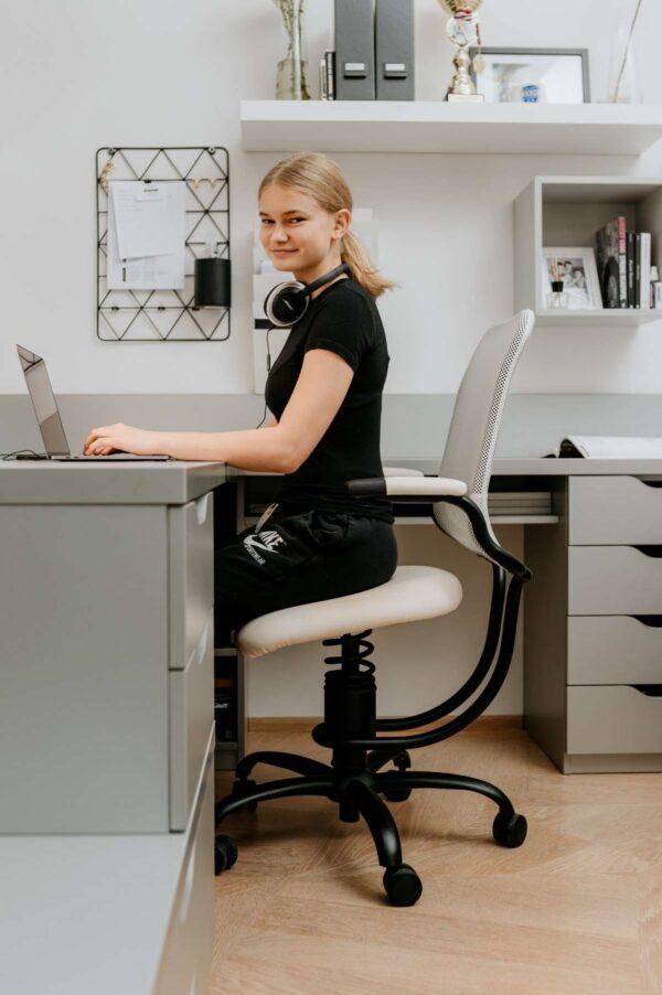Deklica sedi na pisarniškem stolu za mizo
