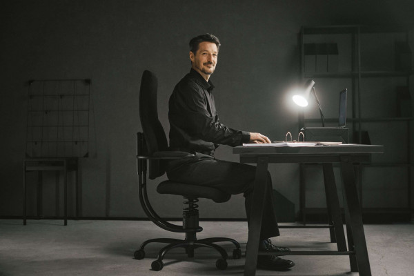 Moški sedi na pisarniškem stolu Navigator posnetek od strani
