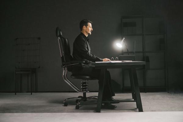 Pisarniški stol pilot v črni barvi slika moškega v pisarni