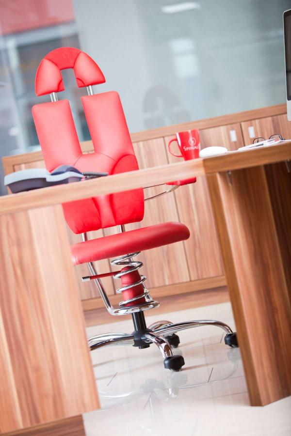 Pisarniški stol rdeče barve v pisarni