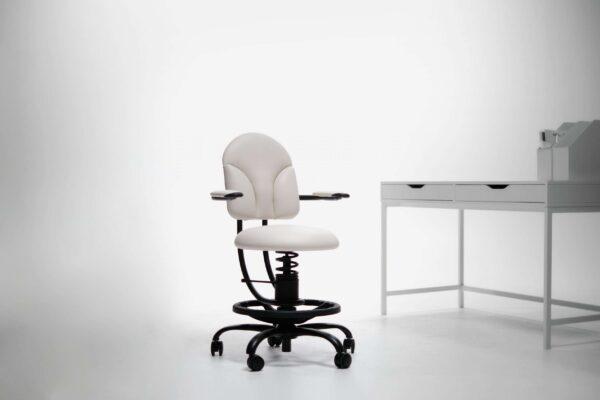 Pisalni stol basic v beli barvi poleg pisalne mize