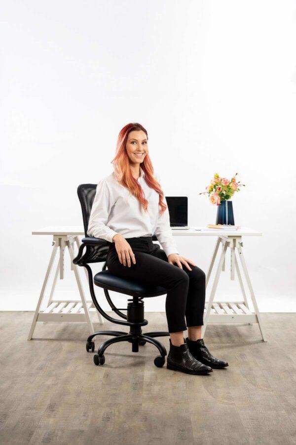 Ženska sedi na pisarniškem stolu Ergonomic