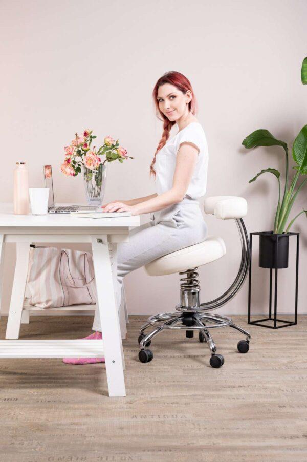 Punca sedi na pisarniškem stolu dent poleg pisalne mize
