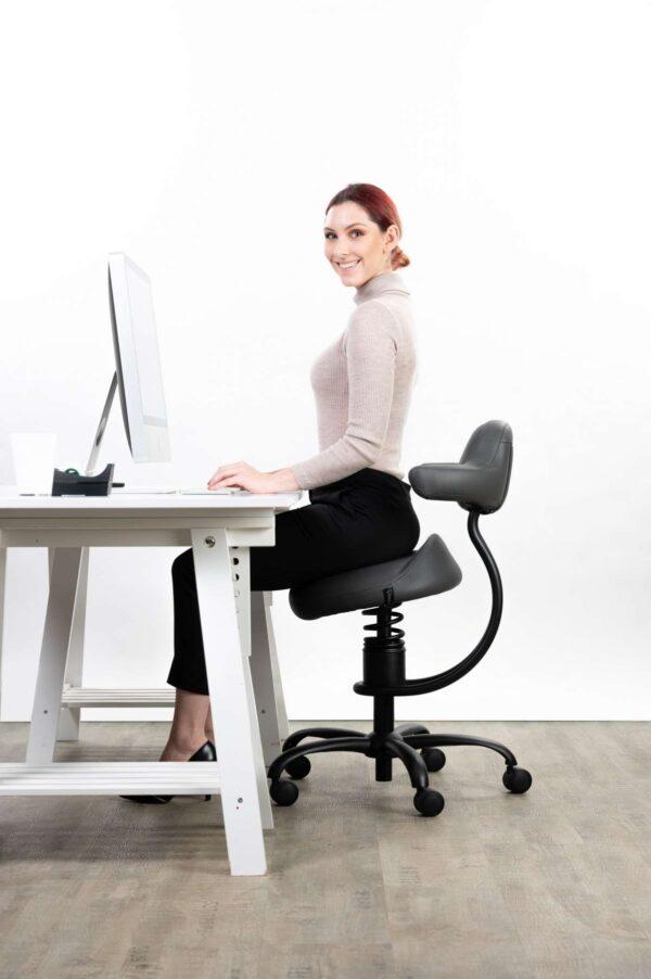 Punca sedi na sivem pisarniškem stolu in dela z računalnikom