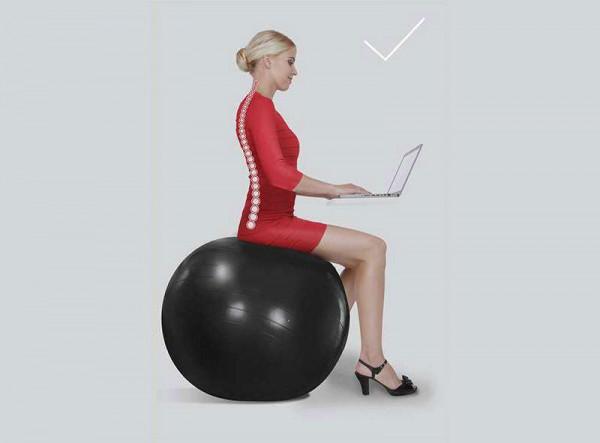 Ženska sedi na terapevtski žogi