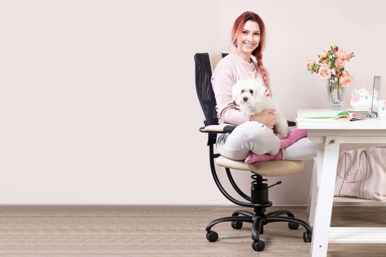 Ženska s psičkom sedi na pisarniškem stolu