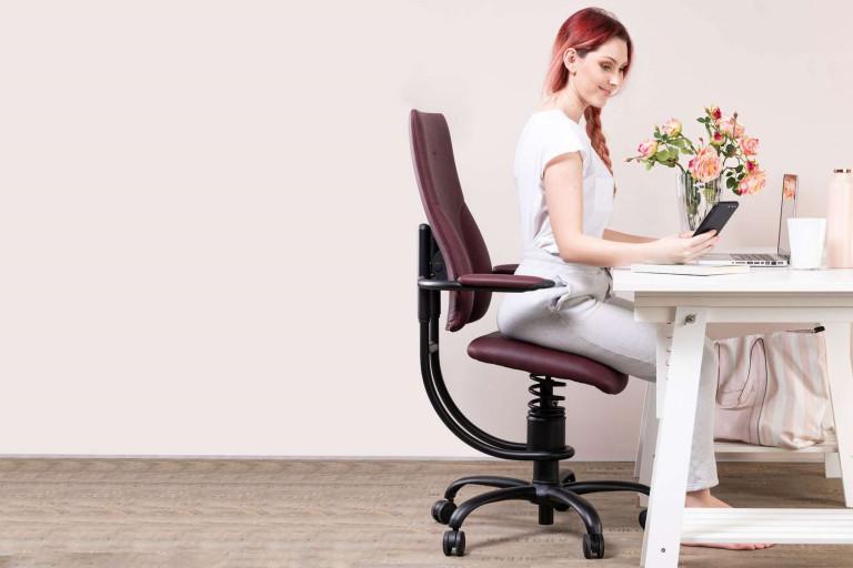 Ženska na pisarniškem stolu gleda v mobilni telefon