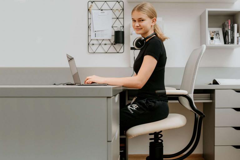 Deklica sedi na pisarniskem stolu in dela z racunalnikom