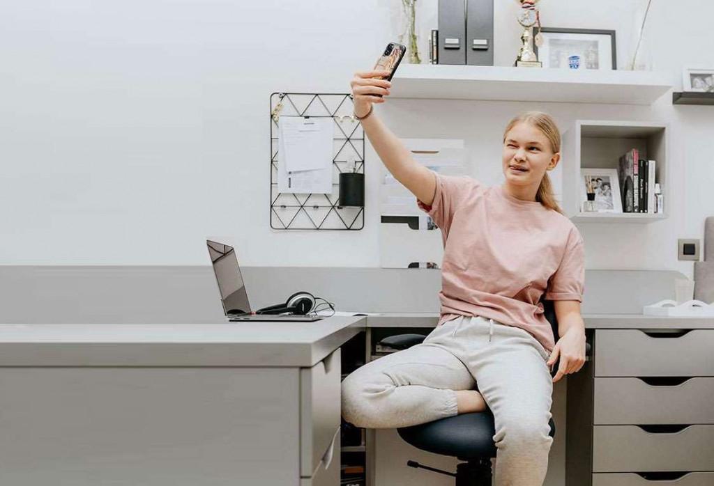 Deklica se slika na pisarniškem stolu