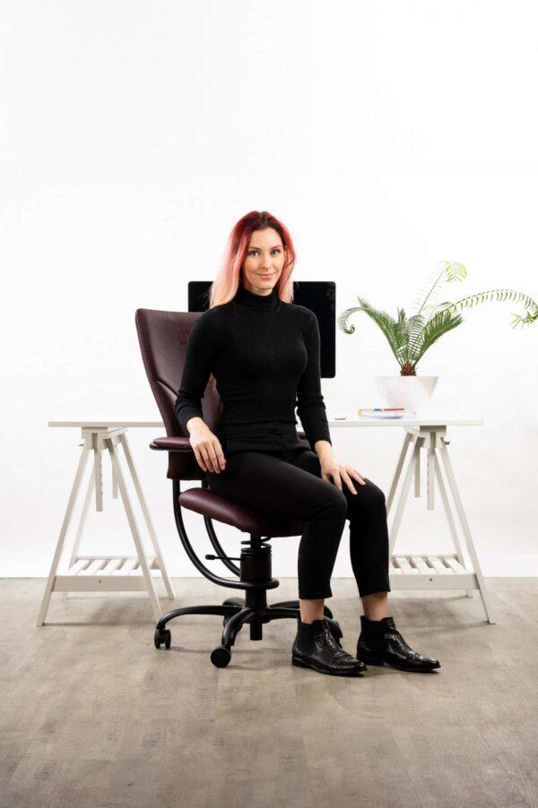 Ženska sedi na pisarniškem stolu Apollo rdeče barve