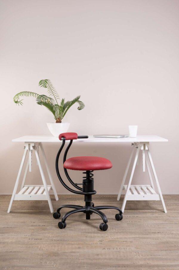 Pisarniški stol Spider rdeče barve zraven pisalne mize