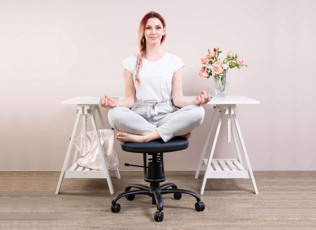 Ženska meditira na pisarniškem stolu